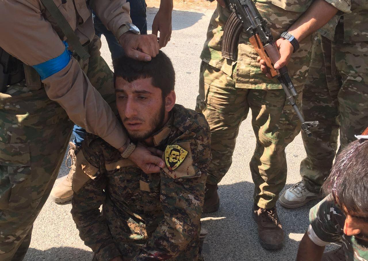 FANGET KRIGER: Dette bildet, sendt ut av det tyrkiske nyhetsbyrået Anadulo, skal vise en kurdisk PKK-kriger fanget av de tyrkisktrente, syriske soldatene. På ermet har han et emblem av den fengslede PKK-lederen Abdullah Öcalan.