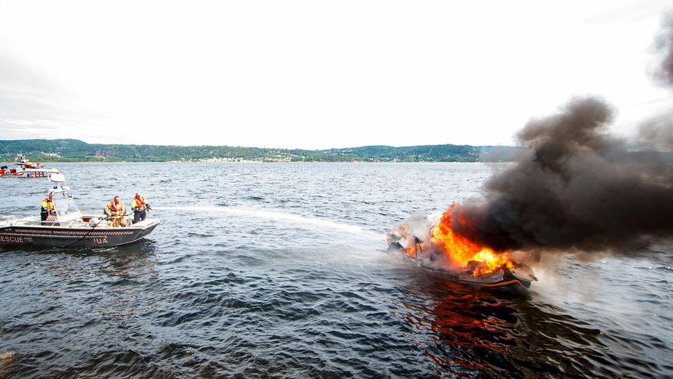 FULL FYR: Brannmannskapet forsøker å slukke brannen på båten til Graham Hansens familie.