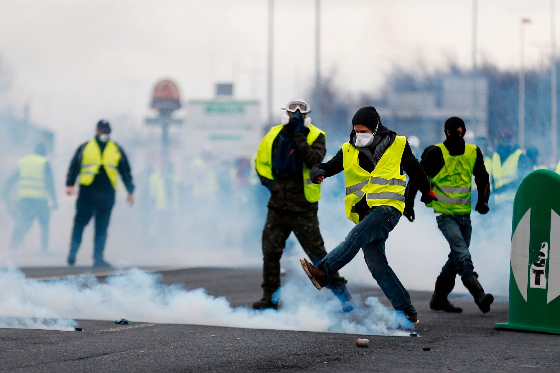 SVARER: Demonstranter fra «de gule vestene» sparker tilbake en kanne med tåregass som politiet har kastet på dem. Bilder er fra byen Caen, nordvest i Frankrike og er tatt 8. desember.