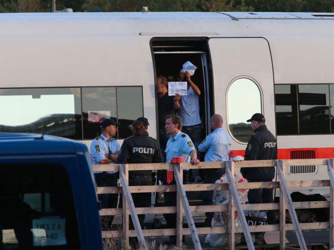 «WE WANT SWEDEN»: Det foregår dialog mellom flyktninger og politifolk i danske Rødby onsdag kveld. Ut fra det VGs reporter kan se står det «We want Sweden» og «We want journalist» på noen av plakatene.