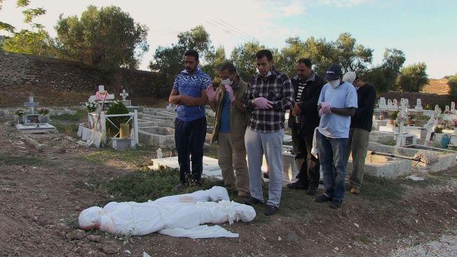 LITEN SEREMONI: En håndfull flyktninger og frivillige sørger over de døde kroppene til en kvinne og et lite barn på kirkegården i Mytilini. Det kan være mor og datter, men ingen er helt sikre. De andre som var i båten sammen med dem da den gikk ned, kjente dem ikke.