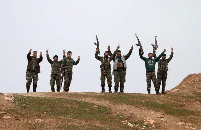 RYKKER FREM: Syriske regimesoldater poserer etter å ha tatt kontroll over landsbyen Kiffin, nord for Aleppo, den 11. februar.