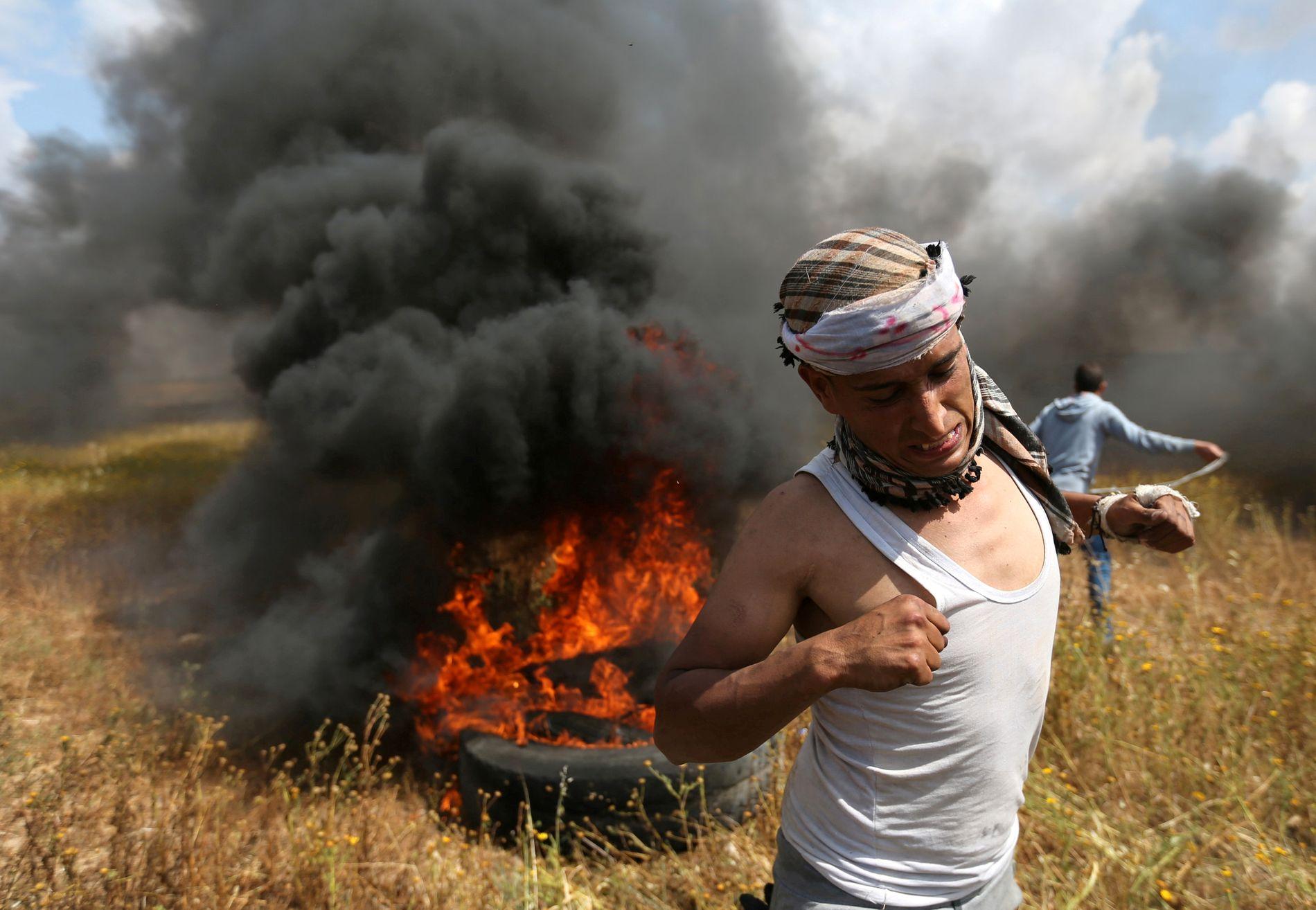 I FYR OG FLAMME: En palestinsk mann løper unna flammene under demonstrasjonen 30. mars.