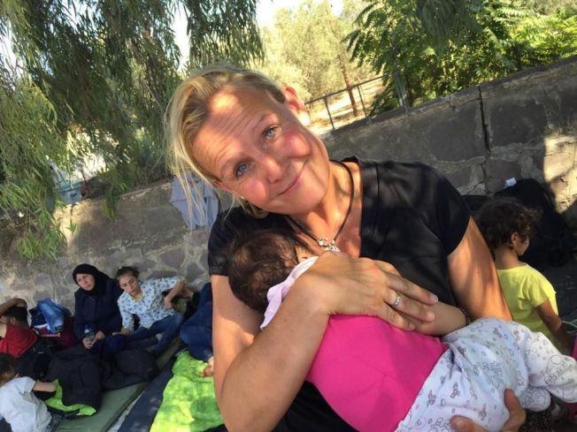 FRIVILLIG: En stor andel av flyktningene som Trude Jacobsen tar imot på stranden på Lesbos er barn. Her holder hun en tre uker gammel baby med kolikk, som nettopp har overlevd ferden fra Syria over Middelhavet, i armene.