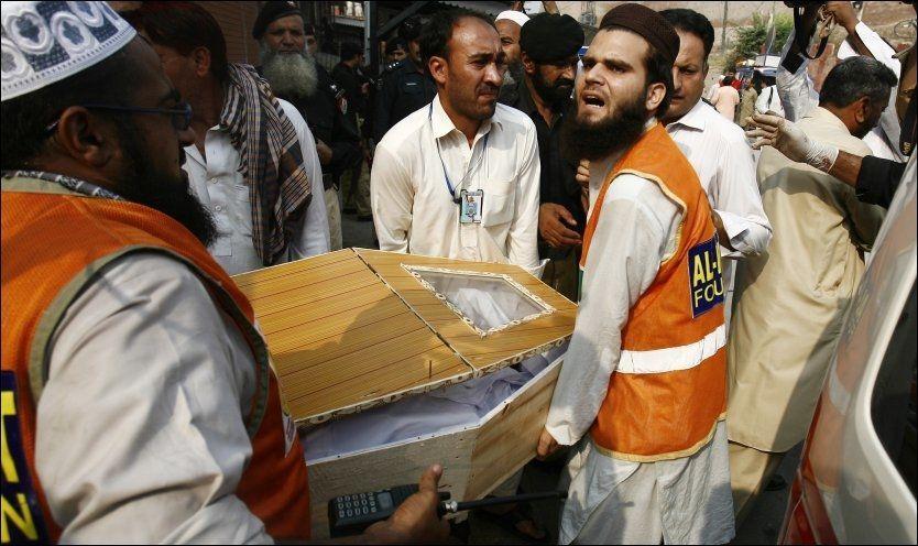 LØFTES BORT: Slektninger og redningsarbeidere bærer kisten til en mann som ble drept i bombeangrepet mot et helsesenter i Peshawar i Pakistan. Foto: REUTERS