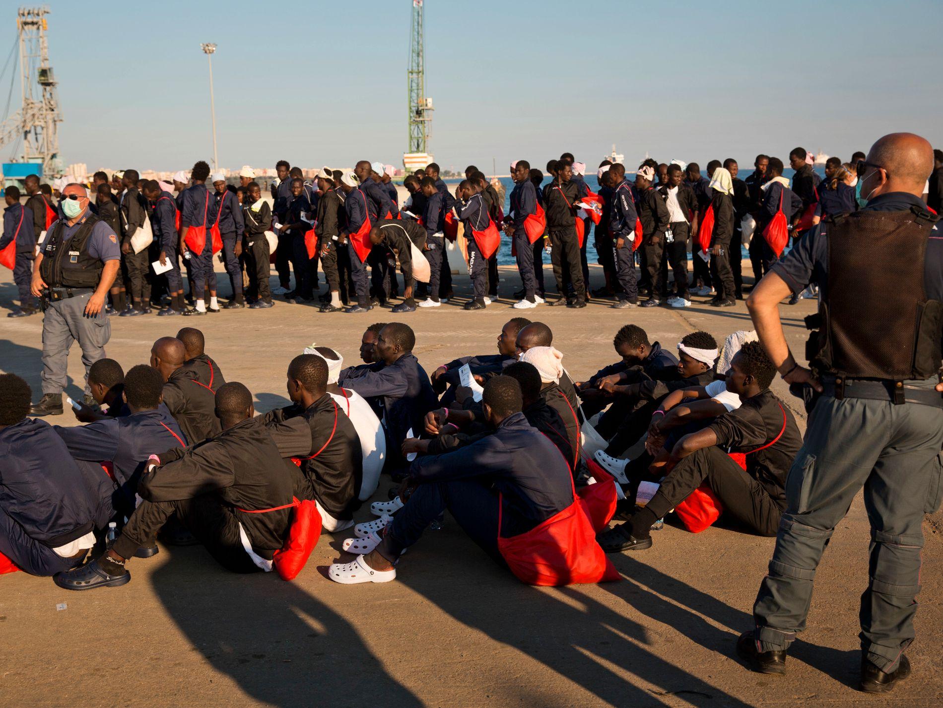 JUNI 2017: Italiensk grensepoliti passer på en ny gruppe båtflyktninger på havnen i Augusta på Sicilia. Foto: AP