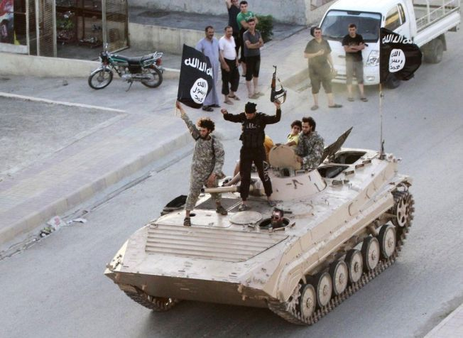 TERRORISTER: Militante islamister viser frem våpnene sine under en militærparade i den selvutnevnte IS-hovedstaden Raqqa i juni 2014.