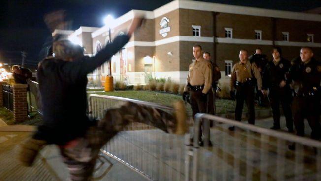 REV NED SPERRINGER: Etter at flere demonstranter gikk til angrep på sperringene som er satt opp utenfor politistasjonen i Ferguson, kom politiet ut for å rydde opp. Da de var satt opp igjen, kom denne demonstranten og sparket i sperringene og ropte «fuck you!».