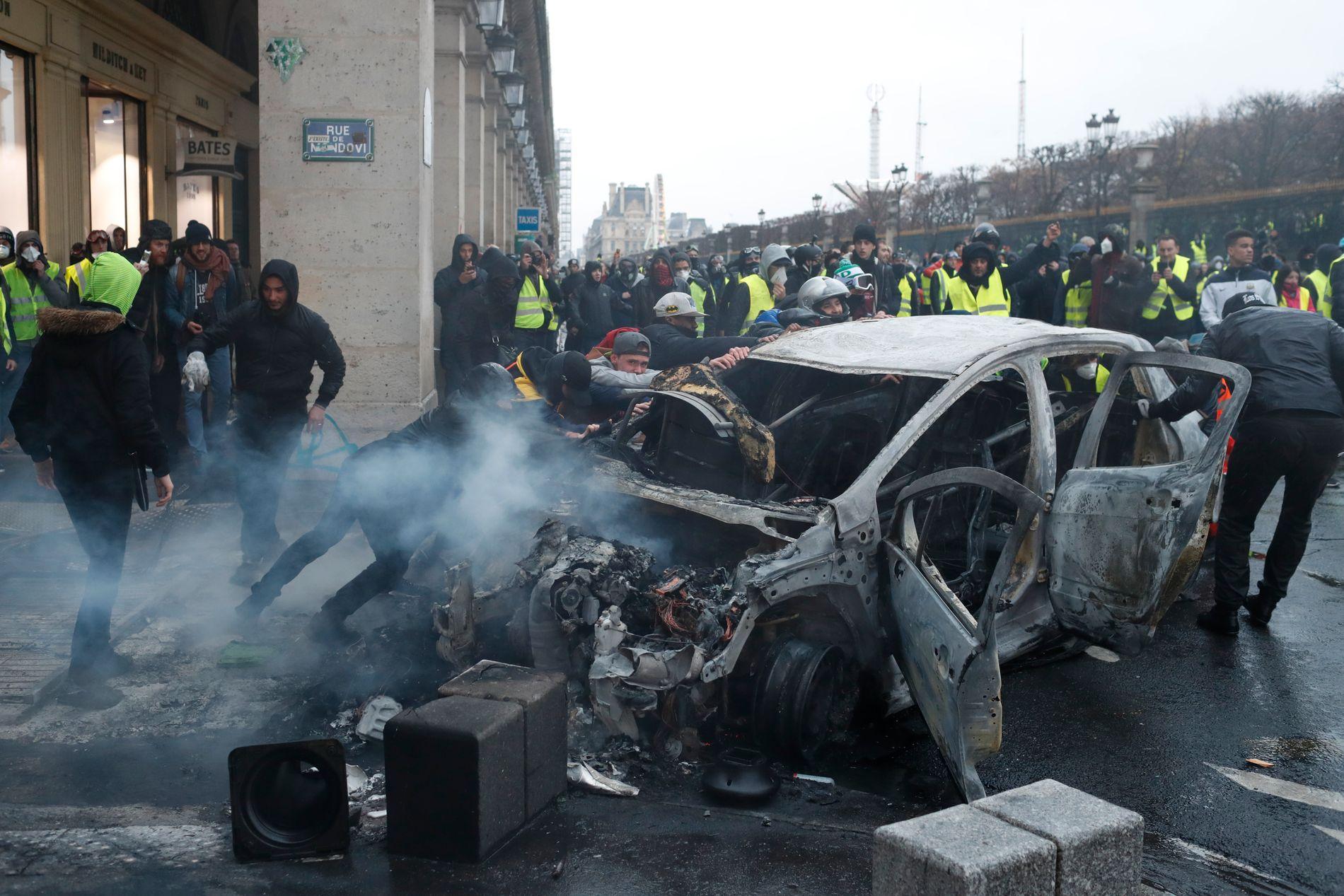 UTBRENT: Demonstranter dytter en utbrent bil under lørdagens protester i Paris