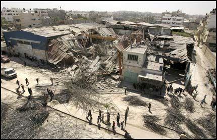 SÅRET: Tre forbipasserende ble såret da Israel skjøt raketter mot denne lagerbygningen i Gaza by lørdag. I andre rakettangrep ble fire palestinere drept. Foto: AP