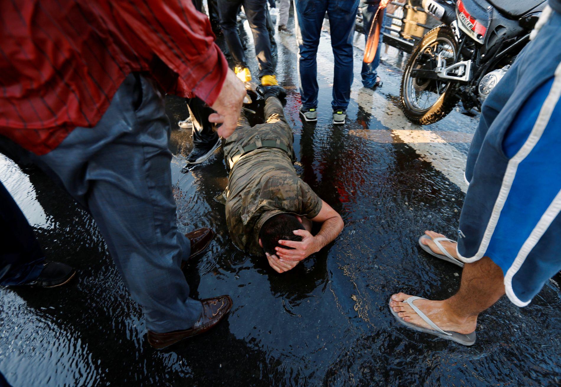 BANKET OPP: En av soldatene som deltok i det mislykkede kuppforsøket prøver å beskytte seg selv etter å ha overgitt seg.