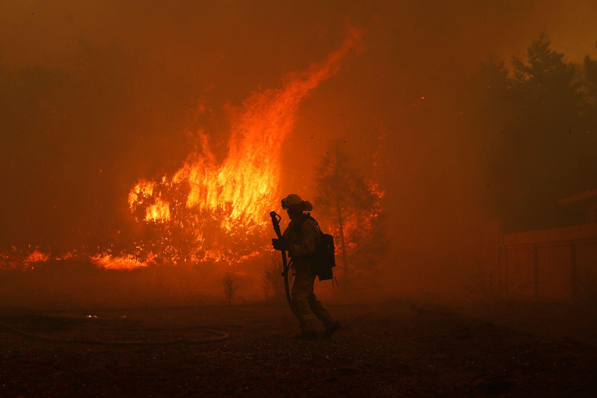 KJEMPER: En brannbetjent slåss mot flammene nær et hjem i Paradise i California torsdag.