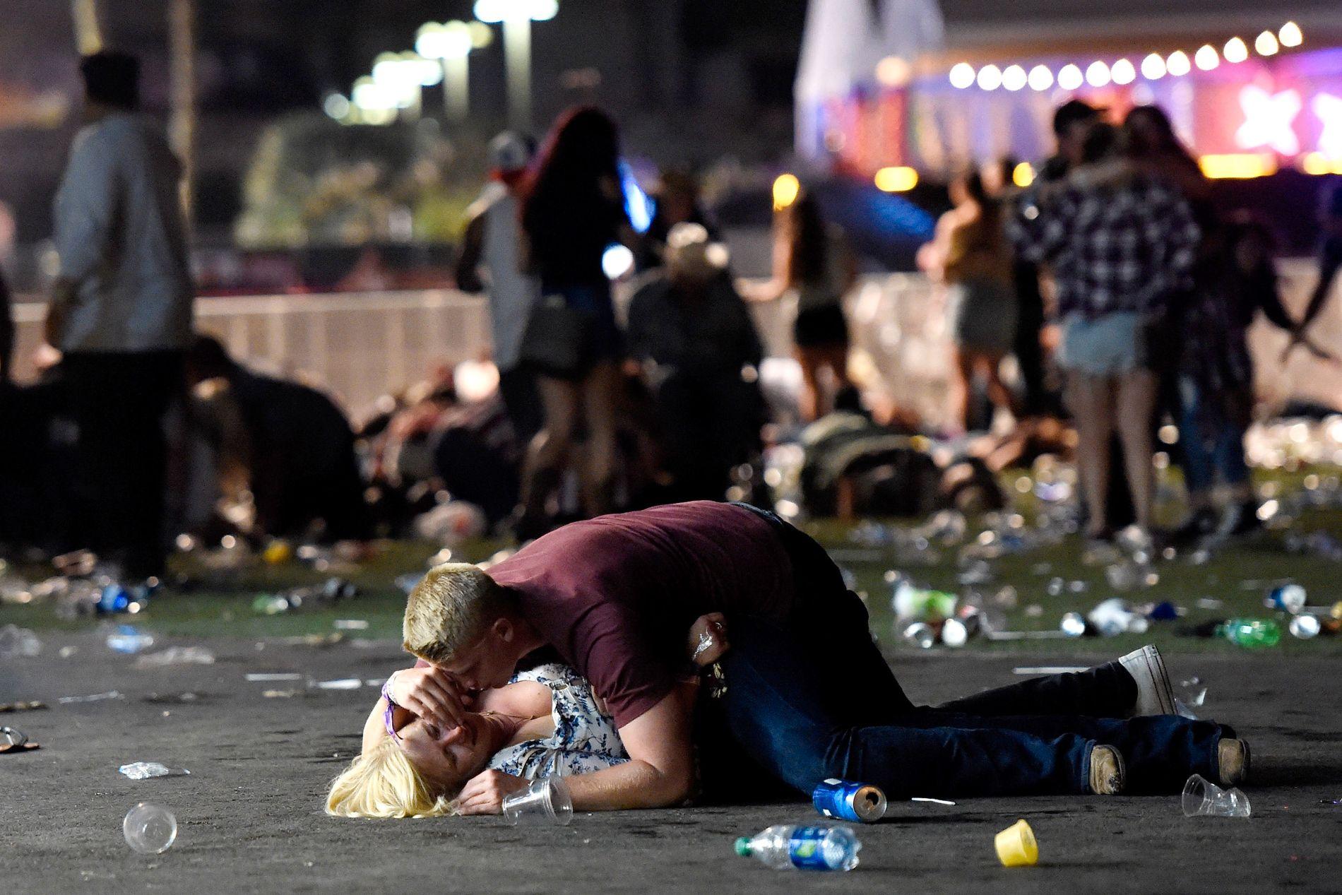 MASSAKREN: En mann ligger over en kvinne mens menneskene flykter vekk fra konsertområdet hvor 59 mennesker ble drept søndag kveld. Fotografen så paret reise seg og gå fra stedet etter bildet ble tatt.