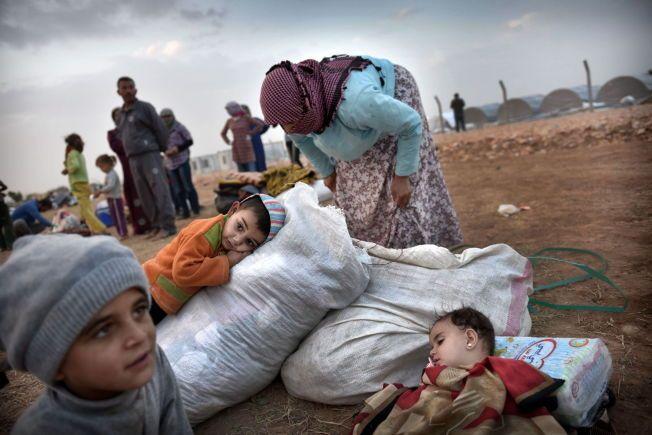FLYKTER: Tusenvis av mennesker flyktet over grensen til Tyrkia da IS angrep kobani i slutten av september. Mange av dem er nå hjemløse. Her er Hamida Hamelo (30), sammen med barna Saleh (3) i oransje og lille Abian (1,5) sovende.