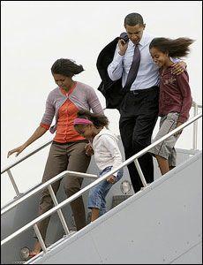 MED DØTRENE: Michelle og Barack har døtrene Malia og Sasha sammen. De har valgt å ikke skaffe seg egen barnevakt, men stoler heller på Michelles mor til å passe barna når de ikke er hjemme. Her er hele familien på vei ut av et fly i Indianapolis i begynnelsen av mai. Foto: AP