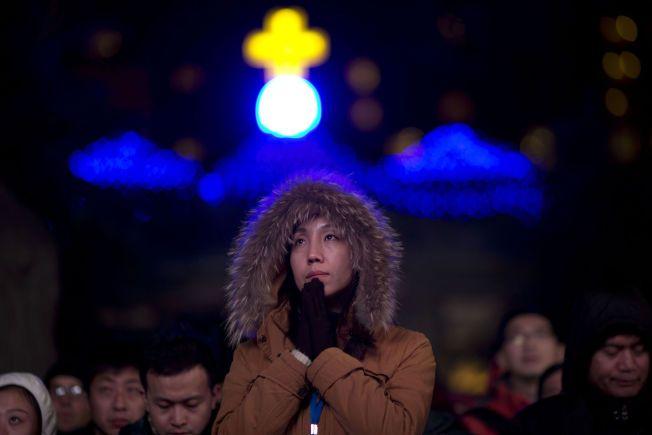 I BØNN: En kinesisk kvinne ber under julegudstjenesten i en offisiell katolsk kirke i Beijing.
