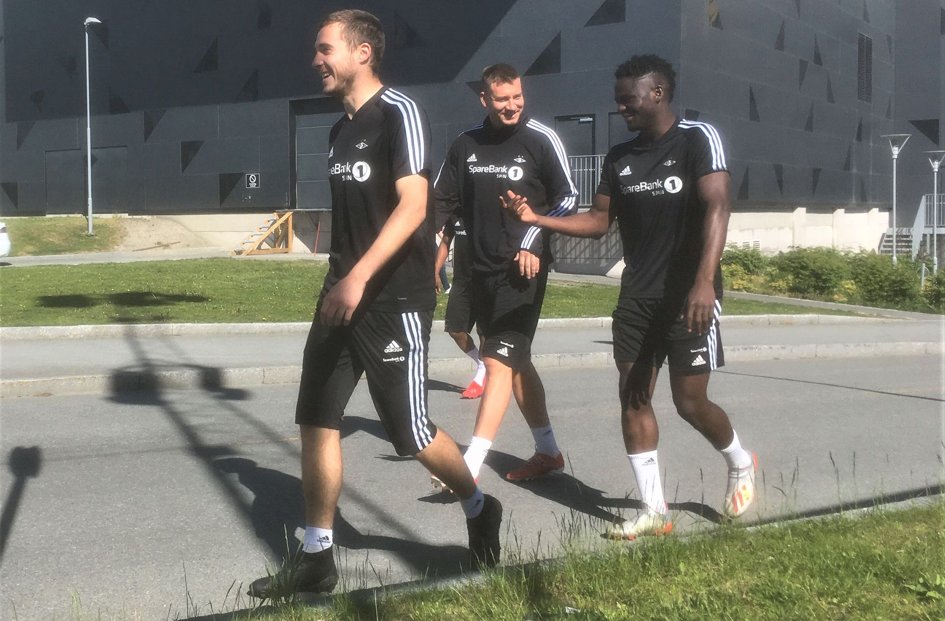 SMIL: Nicklas Bendtner var i godt humør da han ankom RBK-treningen sammen med Dorde Denic (t.v), Samuel Adegbenro (bak Bendtner) og David Akintola (t.h.) i formiddag.