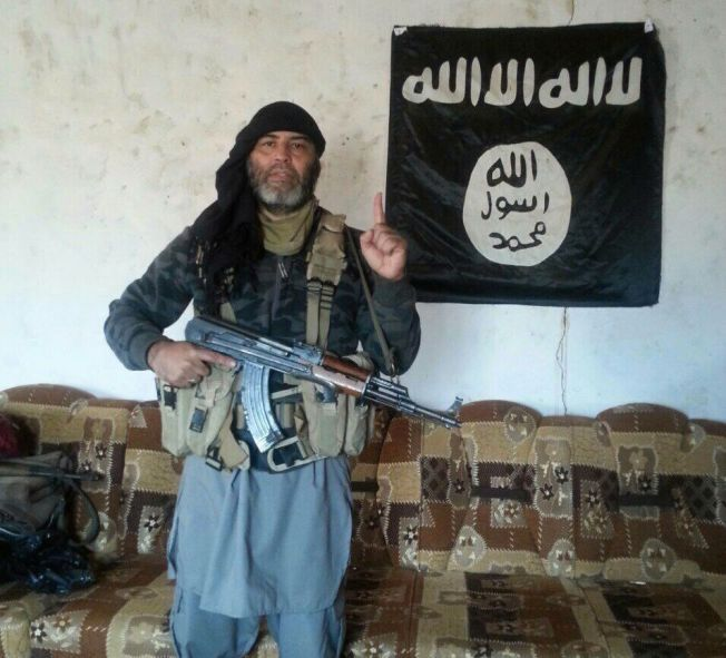 DREPT: Her poserer Omar Cheblal (49) med automatvåpen foran flagget til Islamsk Stat (IS) et sted i Irak, ifølge «Profetens Ummah».