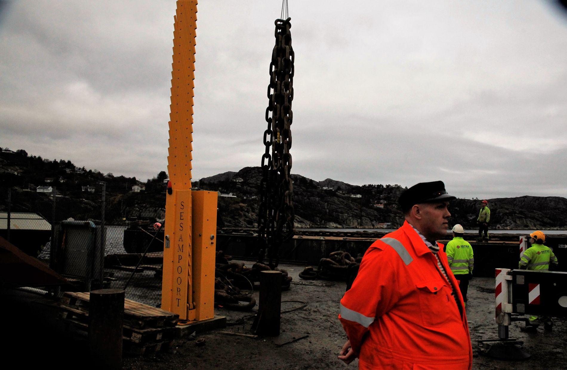 TUNGE LØFT: Her lastes kjettingen som skal heve KNM Helge Ingstad om bord i en lekter som skal frakte den noen kilometer lenger nordover. Bare kjettingen veie 200 tonn.
