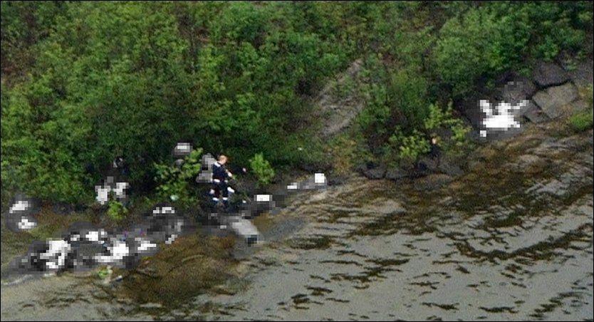 HER SKYTER HAN: Dette bildet viser Anders Behring Breivik i fjæresteinene på Utøya, mens han retter et av våpnene mot ungdom i vannet. Rundt ham ligger flere av ofrene. Foto: Marus Arnesen/NRK