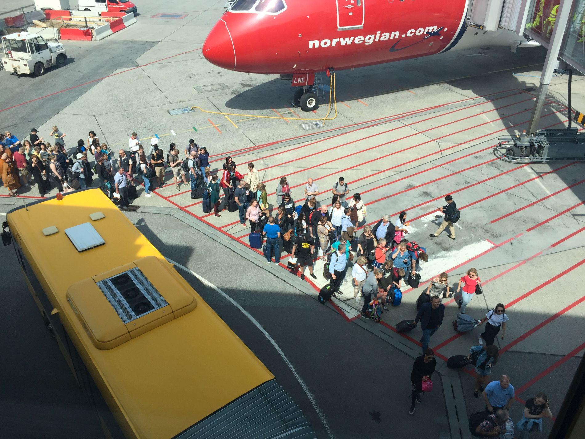 LANG REKKE: Passasjerer i kø ute på Gardermoen flyplass ved 14-tiden i dag. Foto: INGVILD HUNSRØD