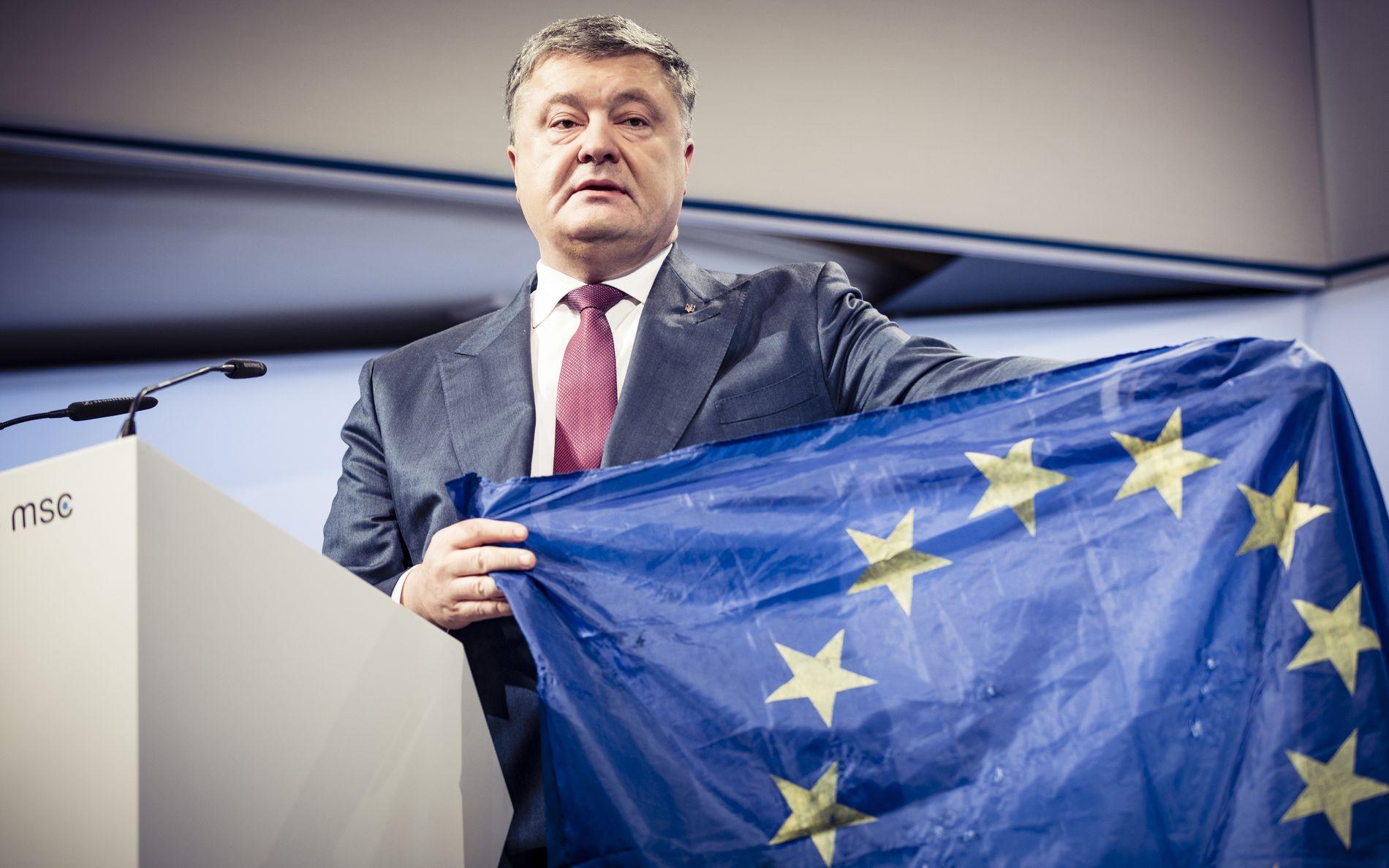 GJENNOMHULLET: Ukrainas president Petro Porosjenko viste frem et EU-flagg med kulehull fra frontlinjen i Øst-Ukraina. – Ikke gå glipp av sjansen til å bygge en mer rettferdig orden i Europa ved å støtte oss. Ved å forsvare Ukraina, forsvarer dere også deres egen suverenitet, territoriale integritet og uavhengighet, sa han til de 500 globale lederne på sikkerhetskonferansen i München.