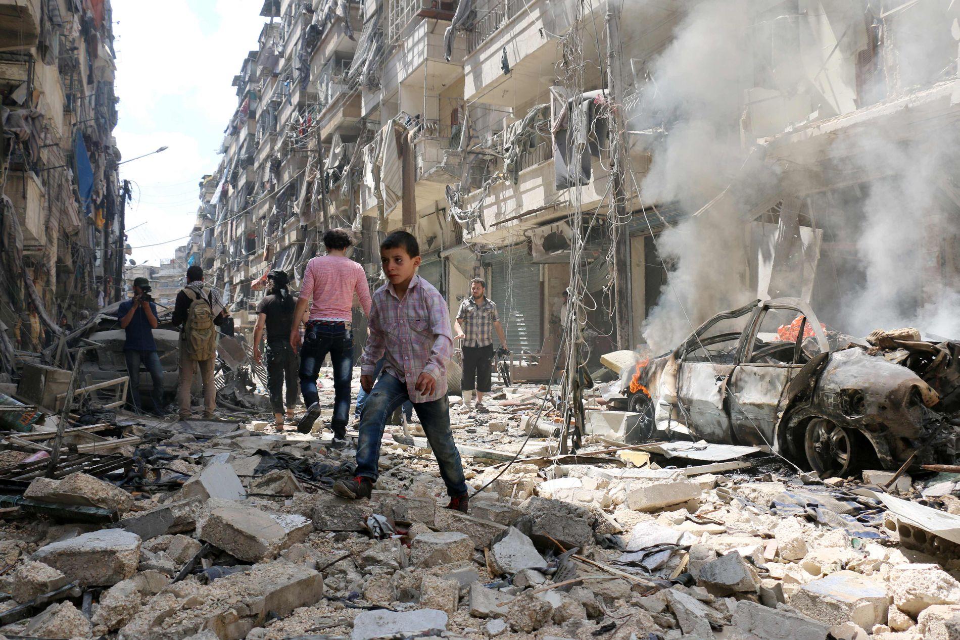I RUINER: Innbyggere ser på de enorme ødeleggelsene etter et luftangrep i den syriske byen Aleppo i slutten av april.