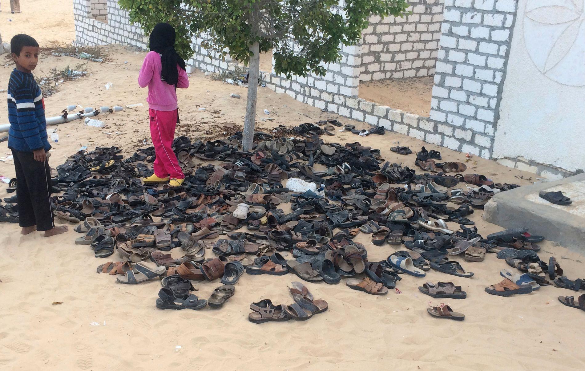 FORLATTE SKO: To barn ser på alle sandalene som ligger igjen utenfor moskeen i al-Rawda i Nord-Sinai, der 305 personer ble drept under fredagsbønn.
