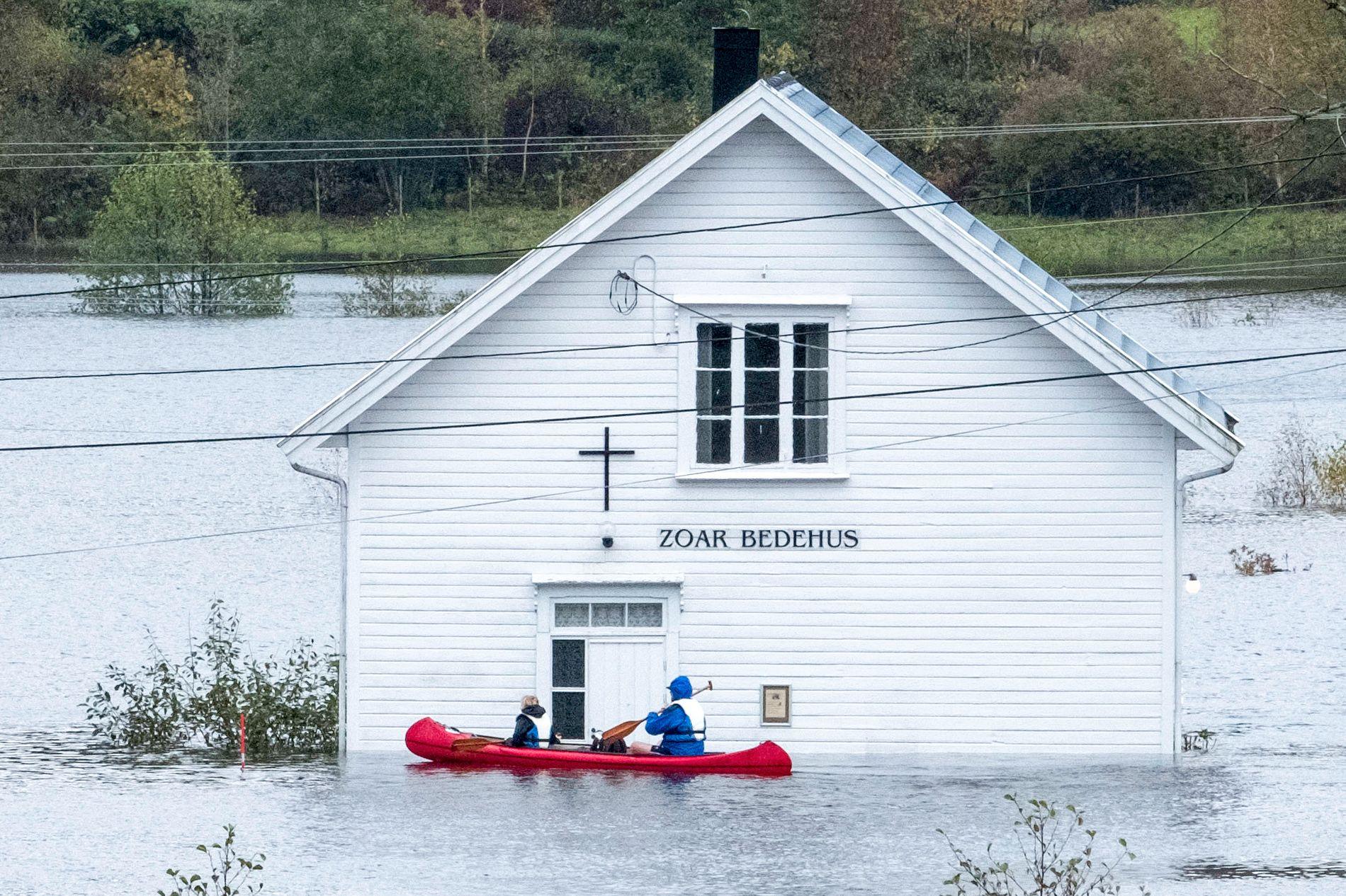 Folk i kano ved bedehuset på Drangsholt langs riksvei 41 mellom Kristiansand og Birkeland som var oversvømt som følge av flommen på Sørlandet i fjor.
