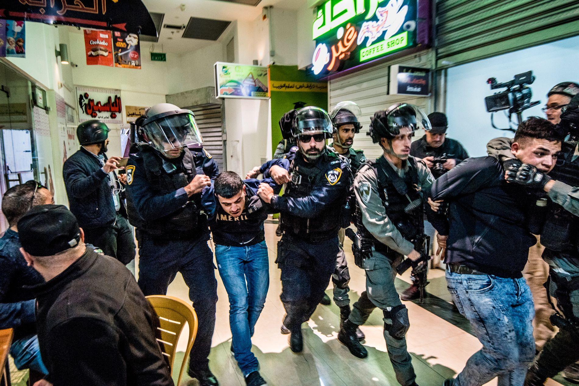 ARRESTERT: Israelske soldater jaget palestinske demonstranter inn på et kjøpesenter i hovedgaten i Jerusalem.