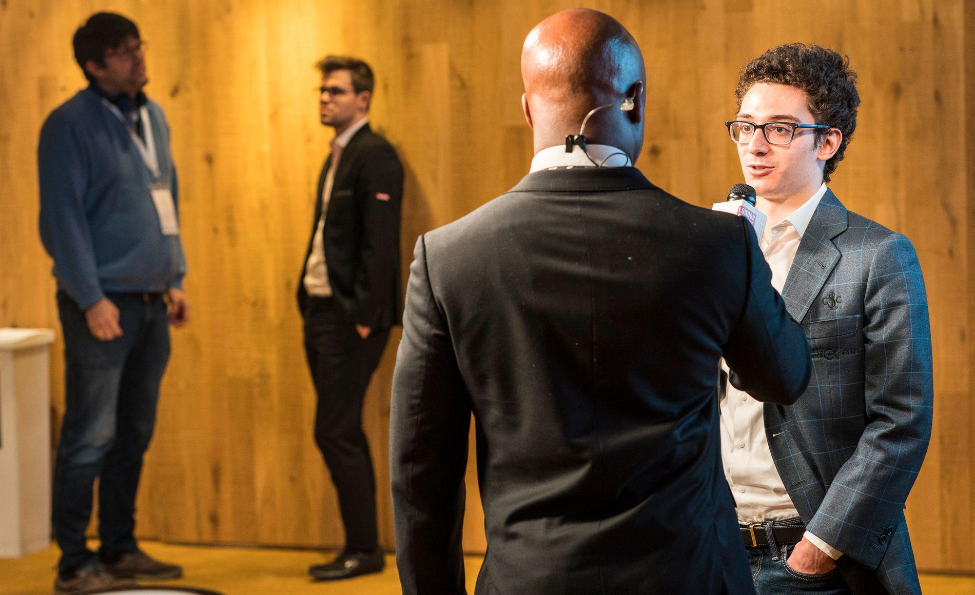RIVALER: Fabiano Caruana (t.h.) intervjuet i forbindelse med møtet med Magnus Carlsen (bak) i St. Louis i høst. Til venstre Carlsens trener Peter Heine Nielsen. Med ryggen til Maurice Ashley.