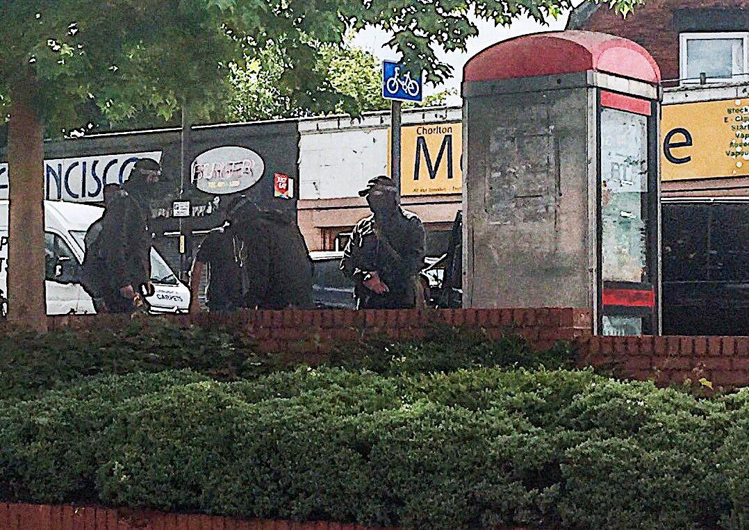 TIL AKSJON: Dette bildet viser en politiaksjon i det sørvestlige Manchester tirsdag formiddag. En person ble ifølge fotografen pågrepet av maskert politi.