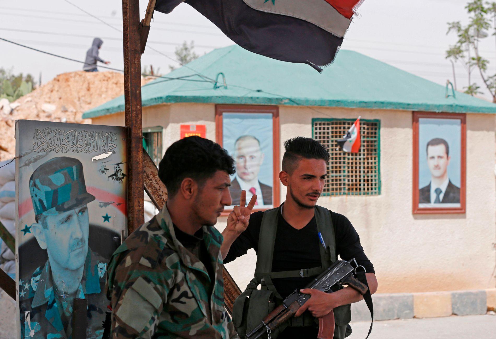 ALLIERTE: To soldater fra den syriske hæren står vakt ved et kontrollpunkt utenfor Damaskus. På veggen bak henger portretter av den russiske og den syriske presidenten.