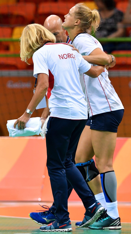 TIDLIG SLUTT: Marit Malm Frafjord måtte støttes av banen etter bare 45 sekunder av kvartfinalen. Lege Anne Froholdt og fysioterapeut Trond Viggo Sjøbakk hjelper henne.