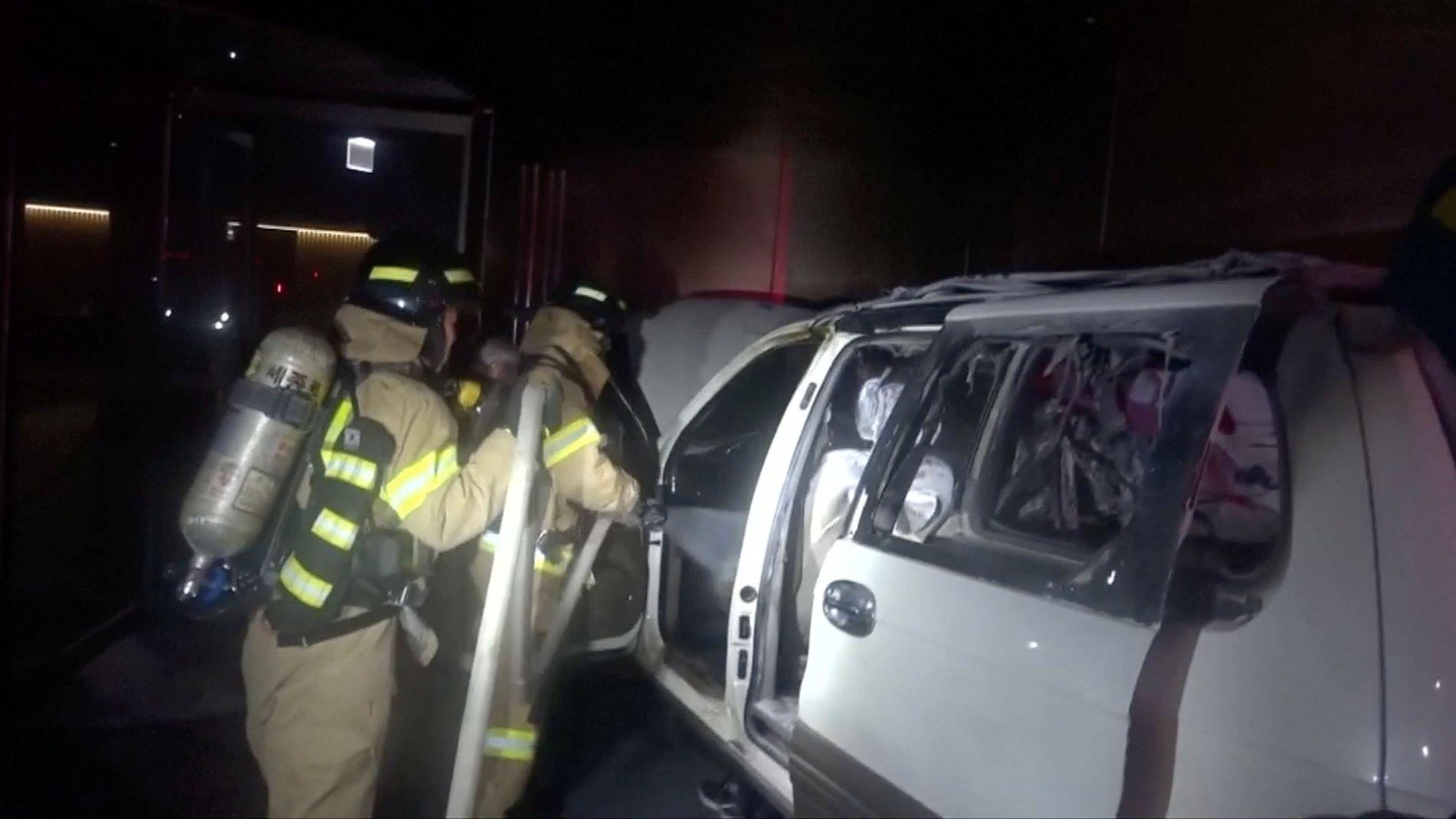 Brannmenn slukker bilbrannen, etter at mannen satte fyr på bilen han selv satt inne i.