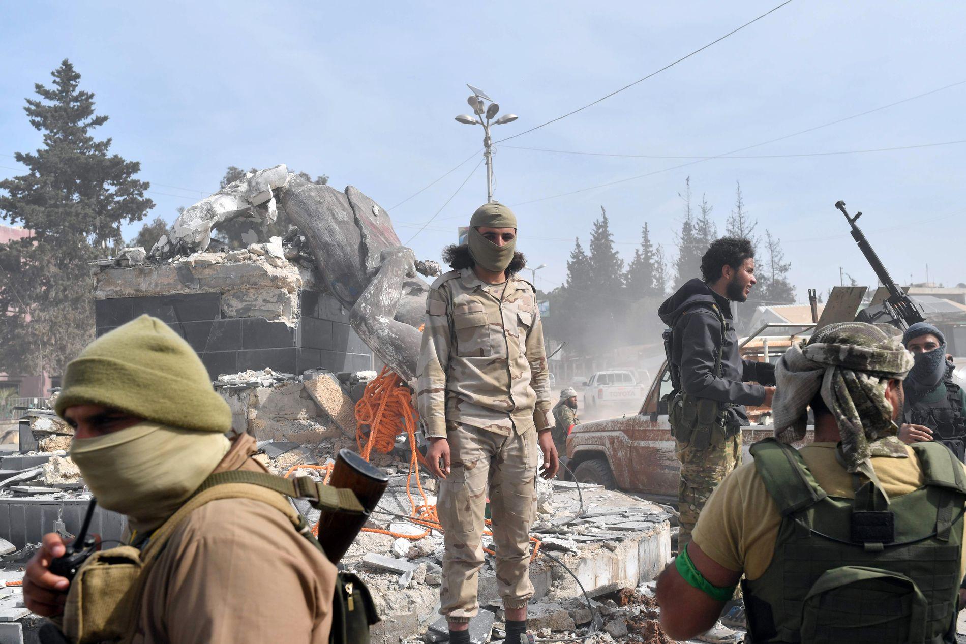 ØDELEGGELSER: Tyrkisk-støttede opprørere har samlet seg rundt en ødelagt statue i Afrin mandag.