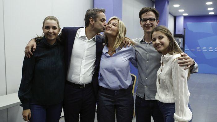 KYSS: Kyriakos Mitsotakis kysser kona Mareva Grabowski på seiersfesten 7. juli, da det ble klart at han hadde vunnet det greske valget. Rundt dem står parets tre barn.