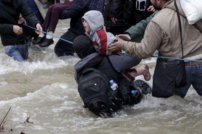 FARLIG VEI: En gruppe migranter hjelper et barn med å krysse grenseelven mellom Hellas og Makedonia.