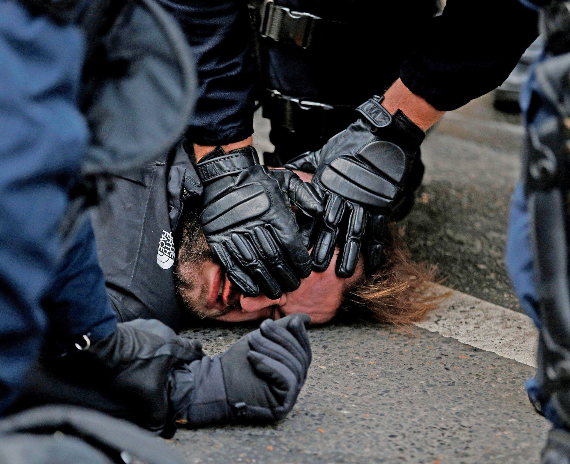 HOLDES NEDE: Franske politistyrker anholder en mann tilknyttet «De gule vestene» i en gate nær Saint Lazare stasjon i Paris.