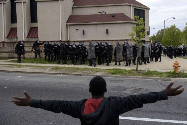 OPPTØYER I BALTIMORE: En ungdom vifter mot opprørspolitiet i Baltimore mandag norsk tid, etter at begravelsen av et mulig politivold-offer utartet til voldelige kamper mellom ungdommer og politiet.