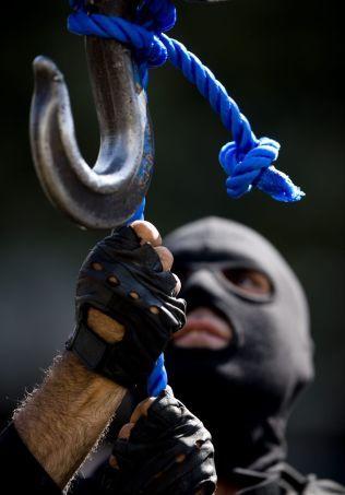 GJØR KLART: Et medlem av Irans spesialpoliti sjekker kabelen som skal henge to dømte menn i Iran i 2007.