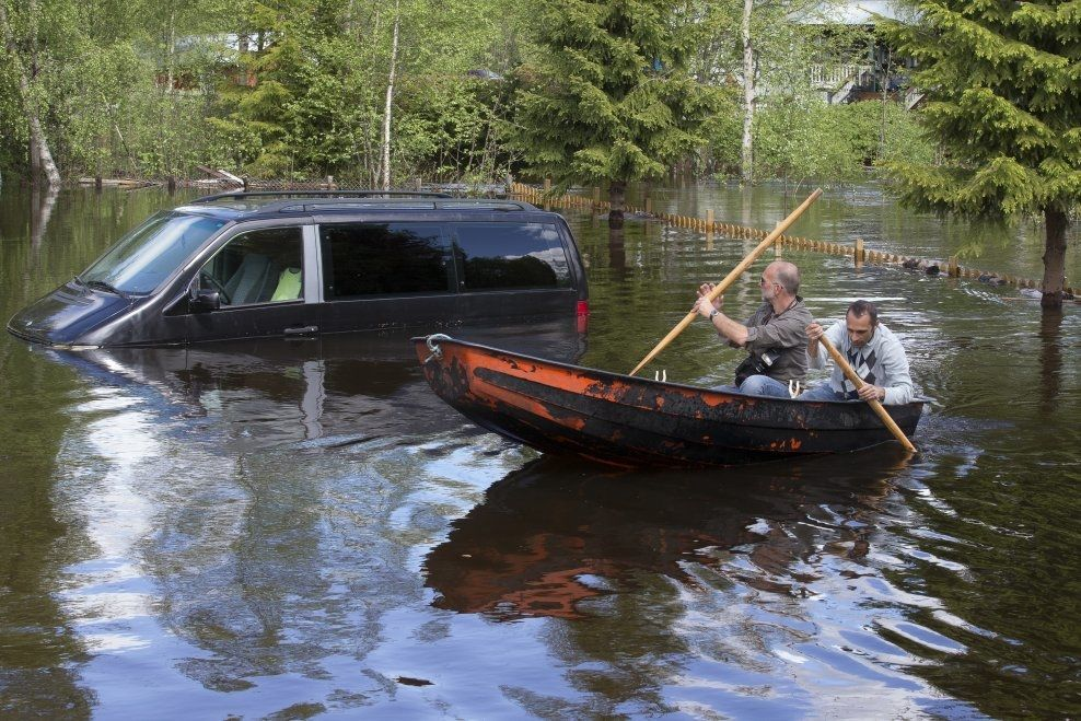 FLOMMEN AVTAR: Mandag måtte Bekem Berati ro i hagen sin i Trysil for å ta en nærmere kikk på bilen han ikke klarte å flytte fra vannmassene. Tirsdag var vannet på vei ned i Trysilelva hvor det var forårsaket flom og store oversvømmelser i Trysil og Nybergsund. Foto: Heiko Junge / NTB scanpix