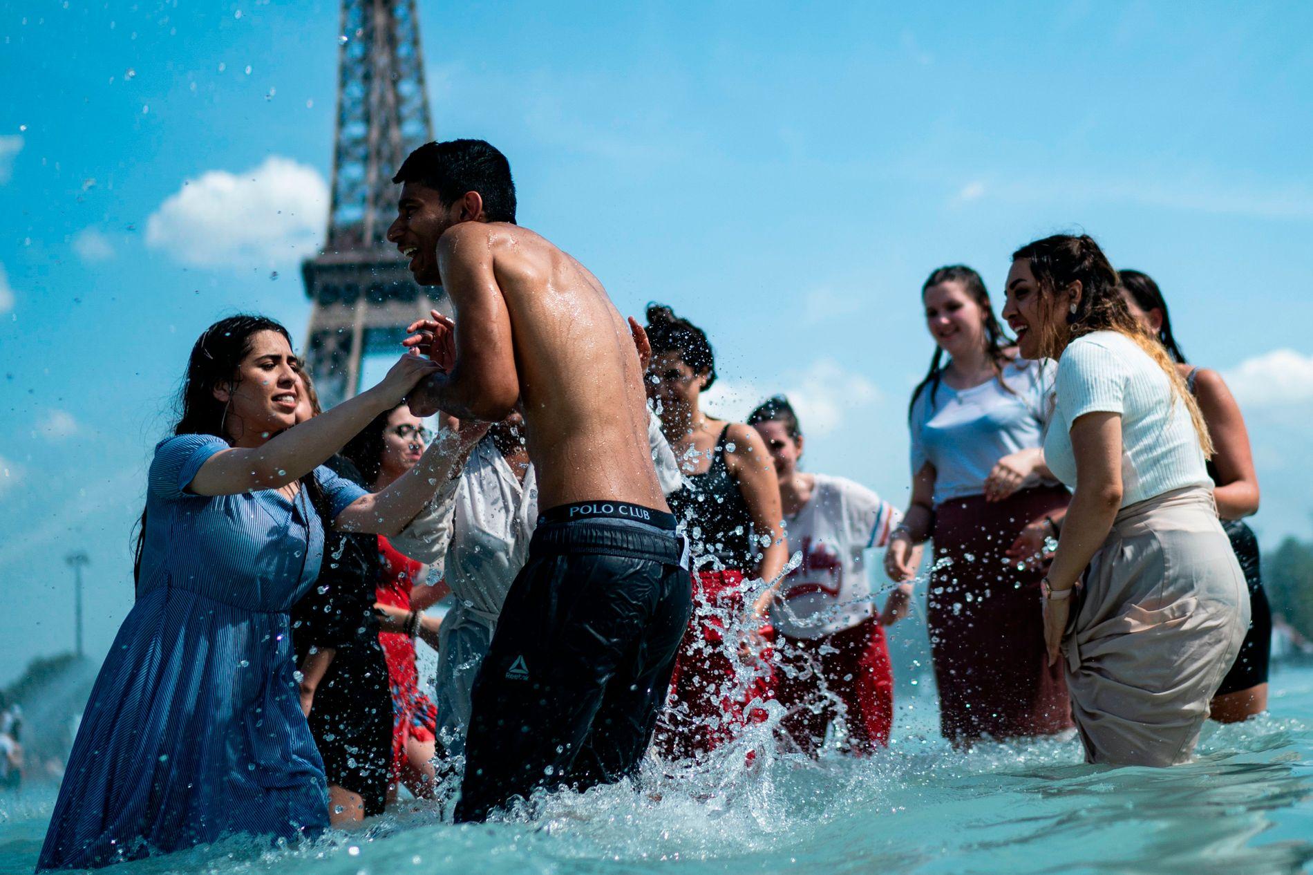 AVKJØLING: Folk benyttet sjansen til å kaste seg ut i fontenene, både med og uten klær, i Paris i slutten av juni.