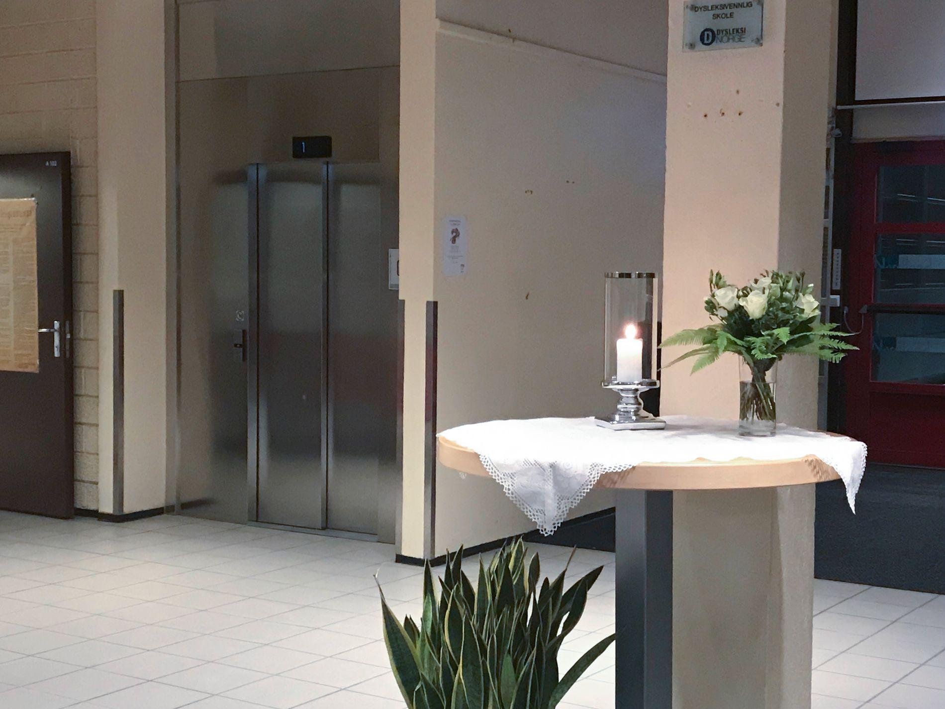 I SORG:  Lys og blomster stå på et bord ved inngangen til Saltdal videregående skole. To elever ved skolen mistet livet i en kollisjon mellom en personbil og en lastebil inne i Saksenviktunnelen på E6 i Saltdal i Nordland.