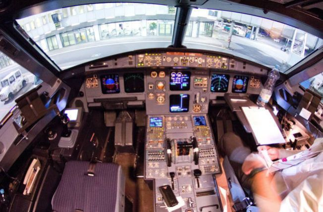 DØDSFLYETS COCKPIT: Dette bildet ble tatt om bord i Airbus A320-flyet fra Germanwings bare noen dager før dødsstyrten. Knappen som låser cockpit-døren er delvis skjult av det som trolig er kapteinens mobiltelefon ved siden av setet til venstre.