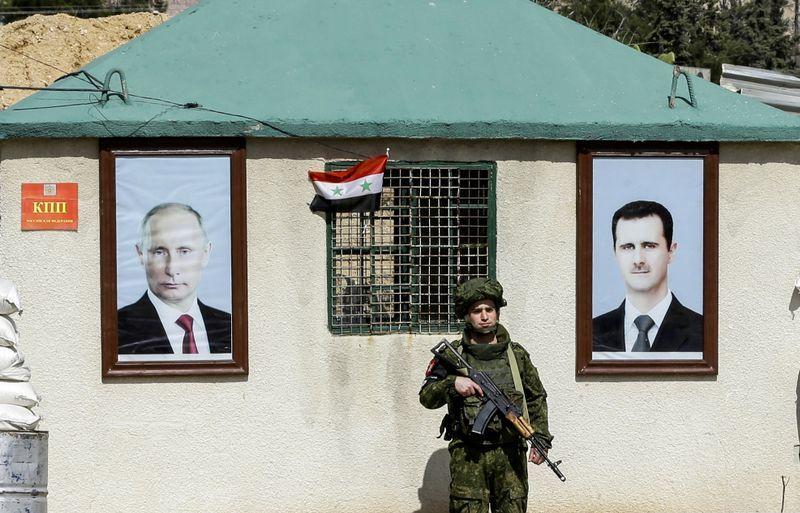 ALLIERTE: En russisk militær politimann står vakt mellom portretter av Vladimir Putin og Bashar al-Assad ved en kontrollpost utenfor opprørskontrollerte områder i Øst-Ghouta.