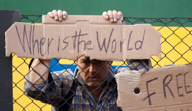 NEKTER Å FORLATE TOGET: Hvor er verden, spør denne mannen. Han er blant flyktningene som nekter å etterkomme politiets ordre. I stedet blir han i og ved toget i Bicske.