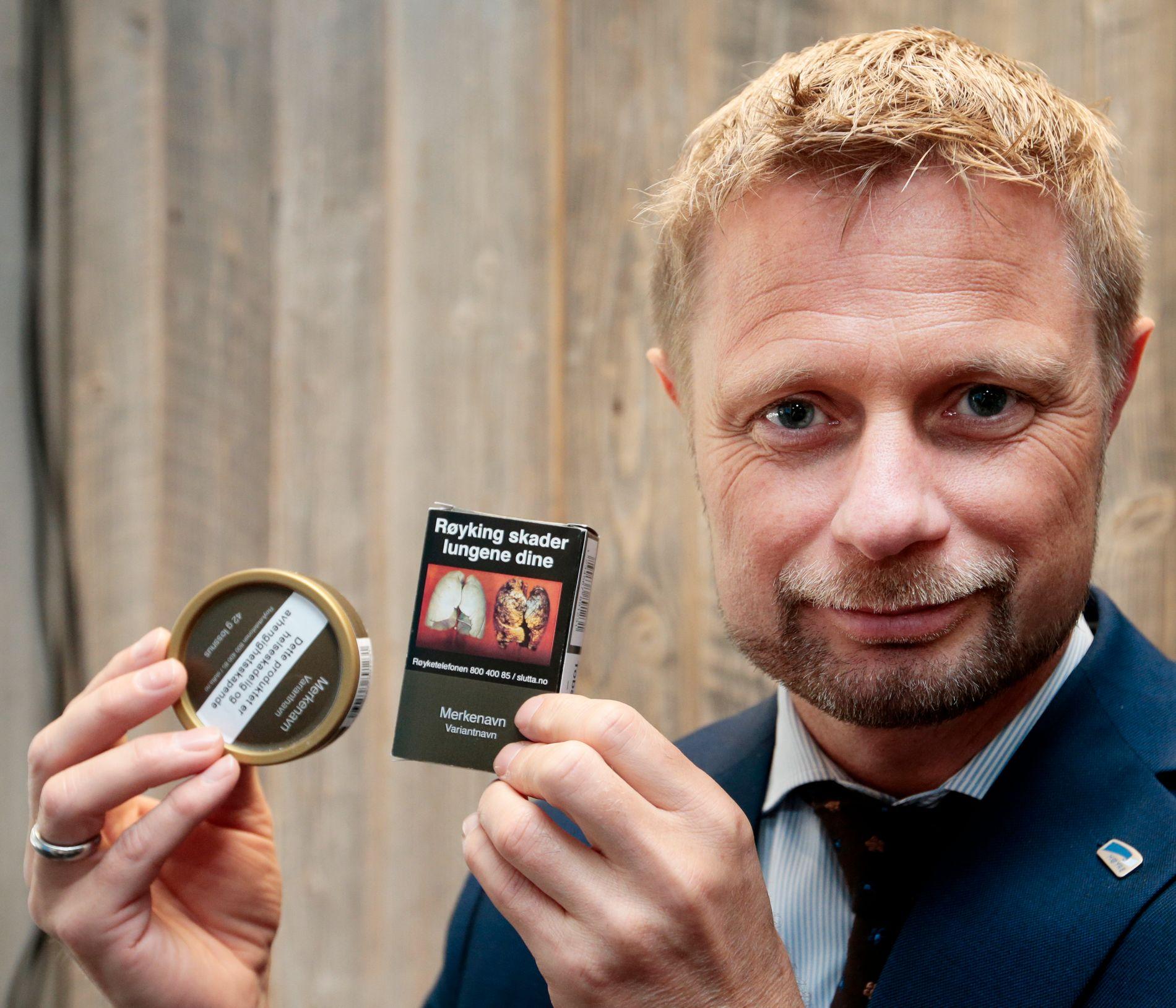 NYTT UTSEENDE: Helseminister Bent Høie (H) viser hvordan røykpakker og snusesker vil se ut i framtiden: Standardisert utseende uten informasjon om smak, styrke, produksjonsdato osv.