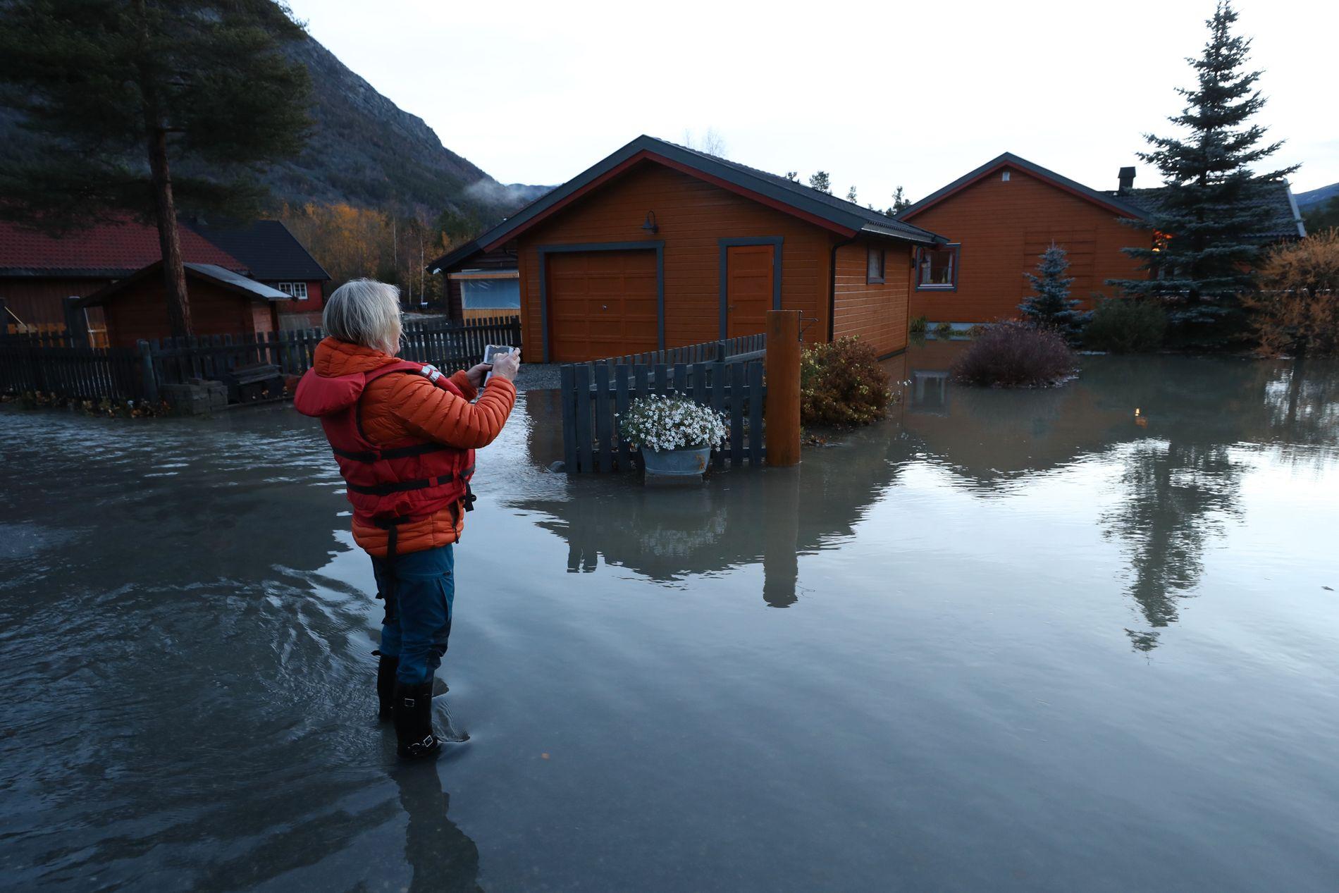 TØRT: Karin Vange tar bilde av huset sitt i Bismo i Skjåk. Hun var blant de første som ble rammet av flommen. Hun takker Gud for at det er tørt inne.