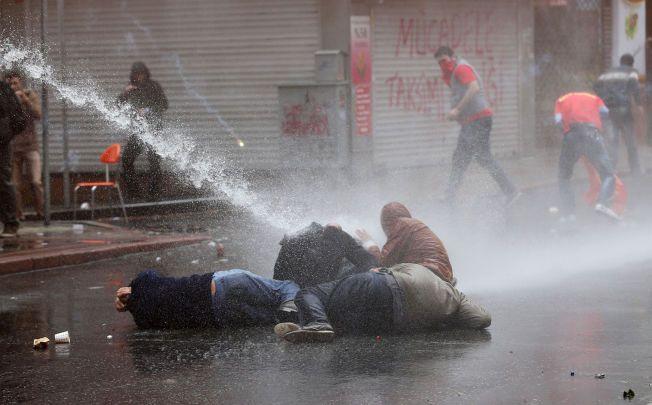 SVARER MED VANNKANONER: Demonstranter forsøker å beskytte seg selv fra politiet vannkanoner under opptøyene i Istanbul 1. mai.
